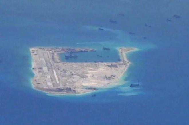 南シナ海の南沙諸島にあるファイアリー・クロス礁。中国艦船とみられる影がみえる=ロイター