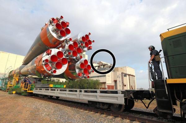 組み立て場から搬出されるソユーズロケット。丸で囲んだ奥の建物の屋根が壊れている=4日、カザフスタンのバイコヌール宇宙基地、鬼室黎撮影