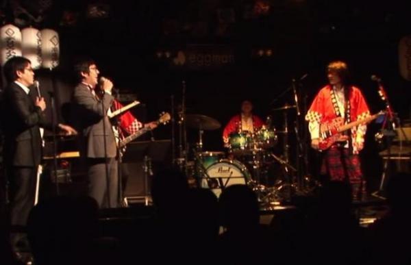 「商店街バンド」のライブ。漫才と生バンドのコラボで客席は笑いに包まれる