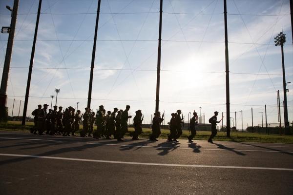 訓練で、銃を手に校内を駆けていく。夕方になり野球部が練習を始めると、かけ声が入り交じった=2016年5月、神奈川県横須賀市、川村直子撮影