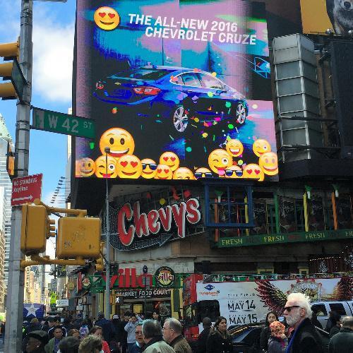 ニューヨークの繁華街タイムズ・スクエアの巨大スクリーンに映し出された絵文字広告。自動車大手ゼネラル・モーターズ(GM)の新型車の宣伝だ=4月27日、ニューヨーク、畑中徹撮影