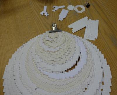 方眼紙をくりぬいた型。くびれのある円筒形なら、大小を何層も組み合わせて表現する