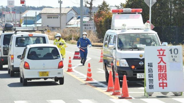 2011年3月27日、福島第一原発から30キロ付近の路上では、この先の20キロ圏内が立ち入り禁止区域だと警察官が案内していた=福島県南相馬市鹿島区