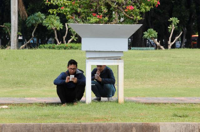 公園で「ポケモンGO」をプレーするインドネシアの青年=2016年7月21日