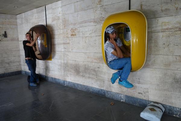 イラン西部ウルミエで、公衆電話を使う人たち。 ボックスに腰けて、もしもーし