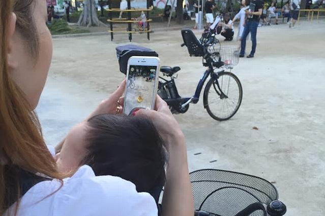 0歳児の子どもを抱えながらポケモンGOをする主婦=24日、東京都墨田区
