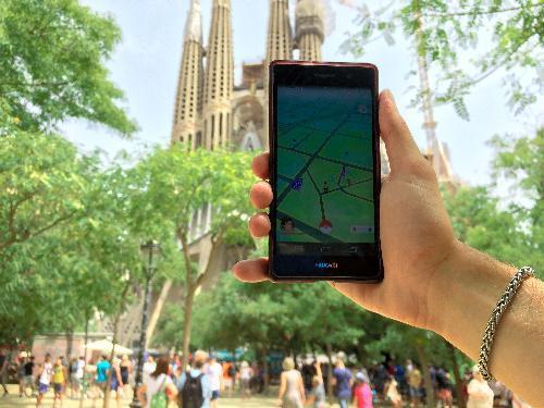 【バルセロナ】スペイン・バルセロナのサグラダ・ファミリア前で、スマートフォンをかざして「ポケモンGO」で遊ぶ男性=2016年7月20日、岩沢志気撮影