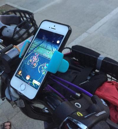片手がふさがるのを防ぐために、自転車にスマホを置く台座をつけた人もいた=24日、東京都墨田区