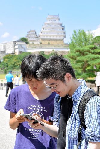 【姫路城】三の丸広場でスマホを手にポケモンを捕まえる大学生ら=2016年7月22日、姫路市本町
