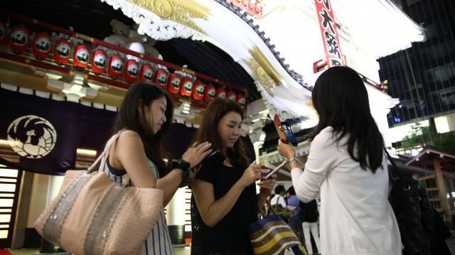 歌舞伎を観覧後、ポケモンGOで遊ぶ女性たち=2016年7月22日、東京都中央区、関田航撮影