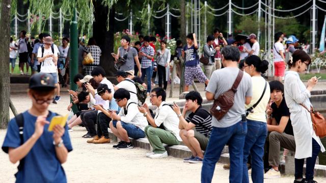 聖地と呼ばれる名古屋市昭和区の「鶴舞公園」で「ポケモンGO」に興じる人たち=2016年7月24日