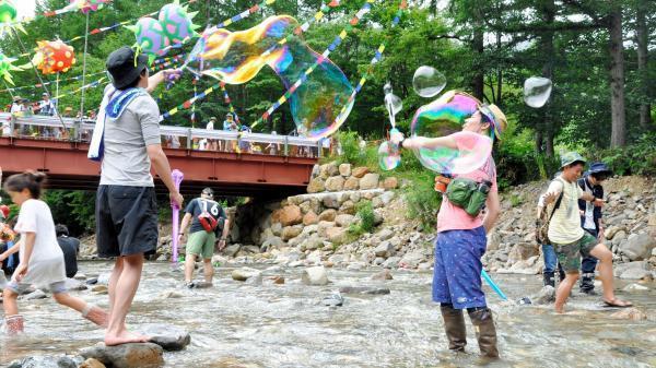 自然と音楽の共生がテーマのフジロック。会場内の川辺には、シャボン玉や水遊びを楽しむ人の姿も=2016年7月22日、新潟県湯沢町の苗場スキー場