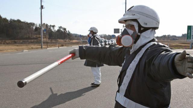 福島第一原発から半径10キロの住民に避難指示が出され、マスクをつけて誘導する警察官=2011年3月12日、福島県富岡町