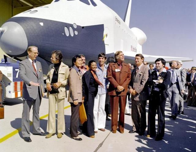 スタートレックからつけられたと言われるNASAのスペースシャトル「エンタープライズ」の前に並んだ初代メンバー。左から、ジェームズフレッチャーNASA長官、ドクターマッコイ役のディフォレスト・ケリーさん、ジョージ・タケイさん、スコッティ役のジェームズ・ドゥーアンさん、黒人女性のウフーラ役のニシェル・ニコルズさん、スポック役のレナード・ニモイさん、原作者のジーン・ロッデンベリーさん、ロシア系のチェコフ役のウォルター・ケーニッヒさん=1976年9月17日、ロイター