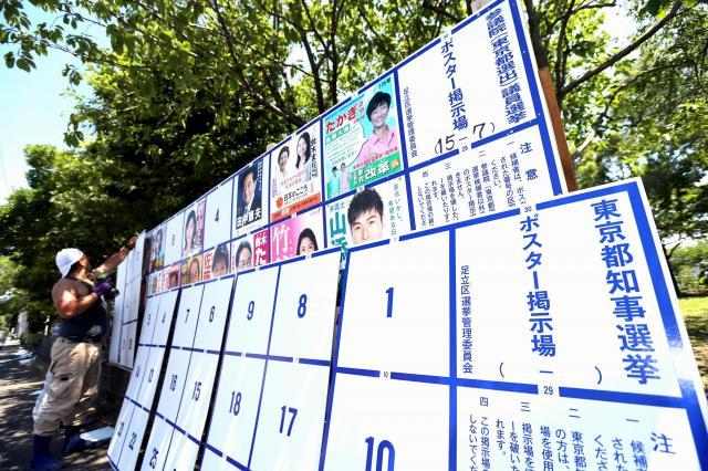 参院選のポスター掲示場の上に、重ねられていった都知事選の掲示場=7月11日、東京都足立区