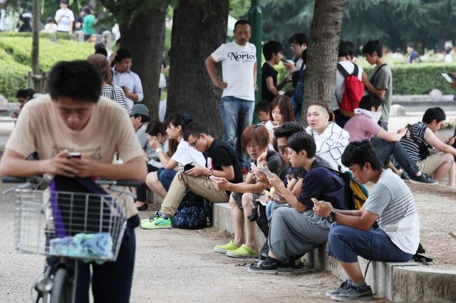 ポケモンGOをする人々。今度は「どう森」する人で町がいっぱいに?=7月24日、名古屋市