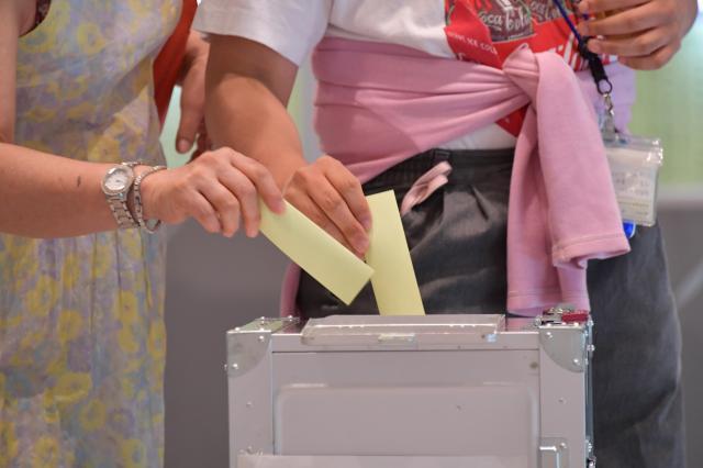 知事選の投票所で票を投じる有権者たち=31日、東京都千代田区