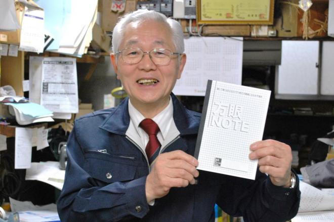 水平に開く自社製ノートを手にする中村輝雄さん