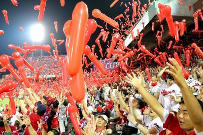 カープ首位独走の熱気に沸く本拠・マツダスタジアムでの観戦風景。ジェット風船を飛ばすファンたち=2016年7月23日