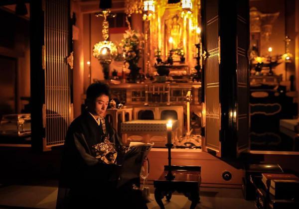 本堂に置かれたろうそくの明かりのもとで #かっこよく新聞読む 極楽寺の住職・麻田弘潤さん