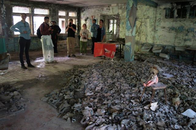 プリピャチの廃墟にある、ガスマスクが敷き詰められたインスタレーションの部屋。参加者たちがガイドの説明に耳を傾ける=水野梓撮影