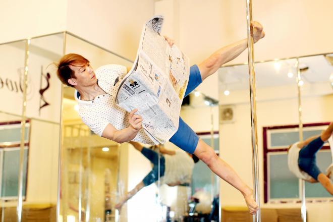 「ポール・スポーツ」の世界大会に出場した中(なか)和也さん(34)。中さんの得意技でもある、足の甲と裏だけでポール上にとどまる技「スターフィッシュ」で#かっこよく新聞読む。
