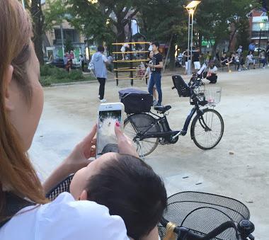 0歳児の子どもを抱えながらポケモンGOをする主婦=7月24日、東京都墨田区