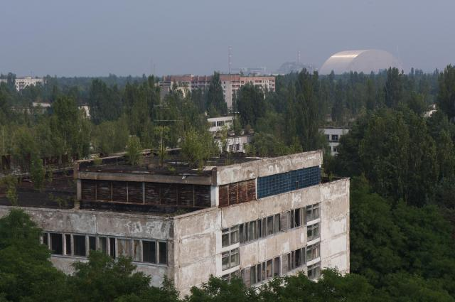 9階建ての廃墟アパートからのぞむ木々に覆われたプリピャチの街。右奥に見える白いカマボコ形の建物が、4号機を覆う予定の新シェルター=水野梓撮影