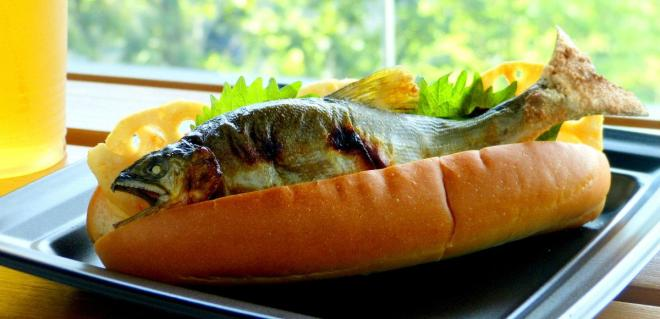 アユの塩焼きドッグ。アユをパンに丸ごと1匹挟んだ商品。8月31日までに期間限定で1日30個のみ。価格は税込み500円