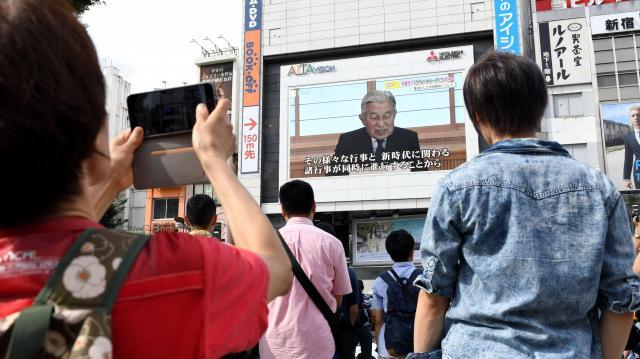 街頭の大画面で天皇陛下のお気持ちを示したビデオメッセージが流され、通りかかった人たちが見上げていた=東京・新宿