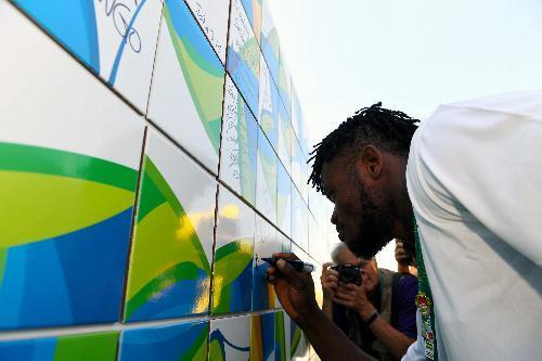 休戦の碑にサインを書き込む難民選手団のポポル・ミセンガ選手=8月1日、ブラジル・リオデジャネイロ、諫山卓弥撮影