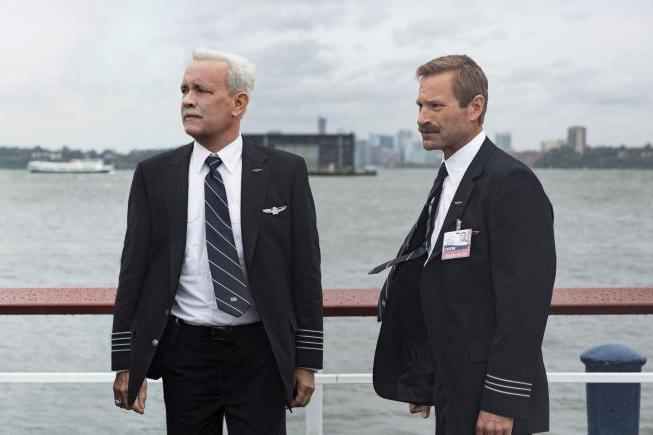 トム・ハンクス演じるサレンバーグ機長(左)。ハドソン川をバックに  ©2016 Warner Bros. All Rights Reserved