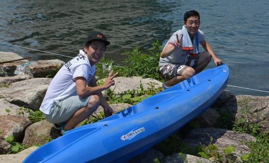 着岸後、カヌーを引き揚げる京都橘大学の学生、林さん(左)と大平さん。