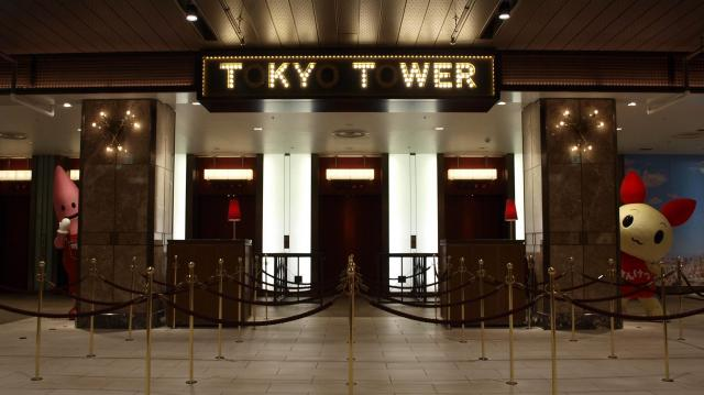 営業時間外に撮影された「O」が消えた東京タワー(Tokyo Tower)のエレベーター乗り場の看板。両脇は東京タワーのゆるキャラ「ノッポン」(写真左)と厚生労働省の献血推進キャラ「けんけつちゃん」