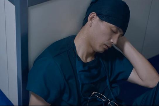 手術後、廊下の隅で仮眠を取る外科医者