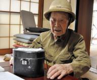 軍隊で身につけていた軍服と帽子をかぶり、飯ごうを手にする元陸軍兵の河原井卓さん=水戸市