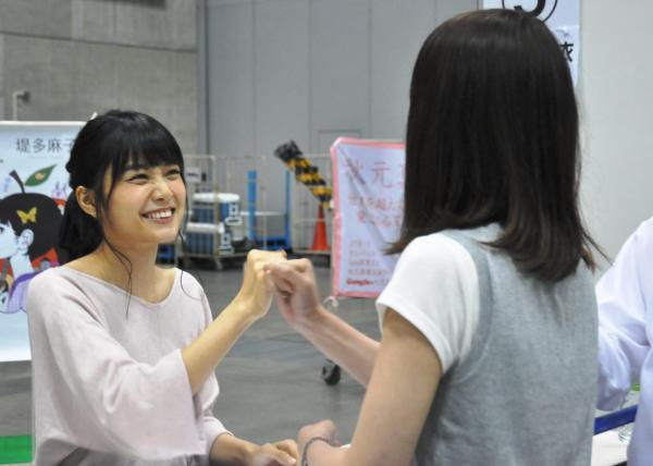 卒業直前の握手会で、ファンと握手する元乃木坂46の深川麻衣さん(左)=6月、横浜市
