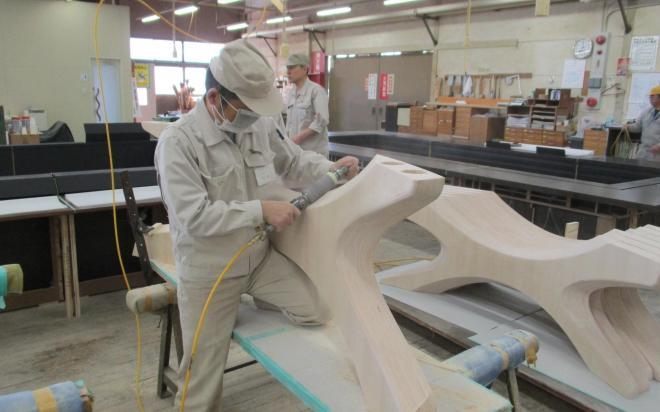 熟練の職人が成形した木材の表面を磨く