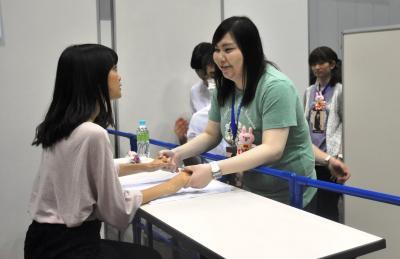 深川さんと握手する勝負澤さん(右)=6月、横浜市