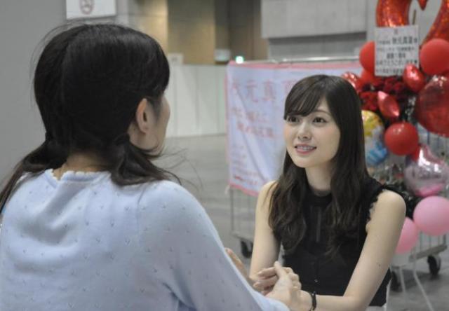 女性ファンと握手する乃木坂46の白石麻衣さん(右)=6月、横浜市