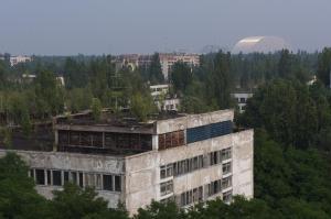 木々に覆われたプリピャチの街を、9階建てのマンション屋上から見下ろす。右奥に見えるのが新シェルター。建物の屋上にも木が生え始めていた=水野梓撮影