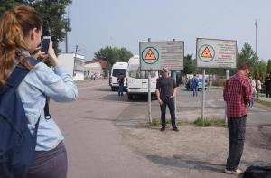 30kmのゲートで、パスポートをチェックされる。看板前で写真を撮る参加者たち=水野梓撮影
