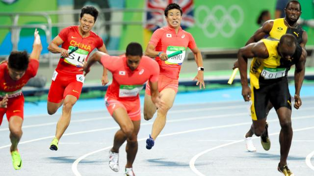 男子400メートルリレーで第4走者のケンブリッジ飛鳥(中央)にバトンを渡す第3走者の桐生祥秀(後方)=林敏行撮影