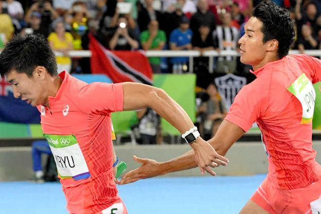 男子400メートルリレー決勝 第2走者の飯塚(右)から第3走者の桐生へリレー=代表撮影