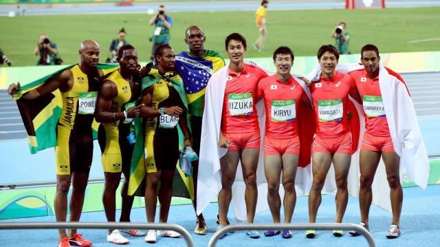 男子400メートルリレーで銀メダルを獲得し、優勝したボルト(左から4人目)らジャマイカチームと記念撮影する(右から)ケンブリッジ飛鳥、山県亮太、桐生祥秀、飯塚翔太=19日、五輪スタジアム、林敏行撮影