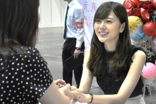 女性ファンと握手する乃木坂46の白石麻衣さん(右)