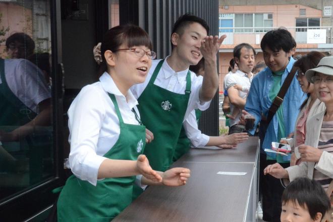 こちらは通常のグリーンのエプロン(2015年、営業開始前の記念行事で、スターバックスのアイスコーヒーなどを受け取る人たち=鳥取市東品治町)