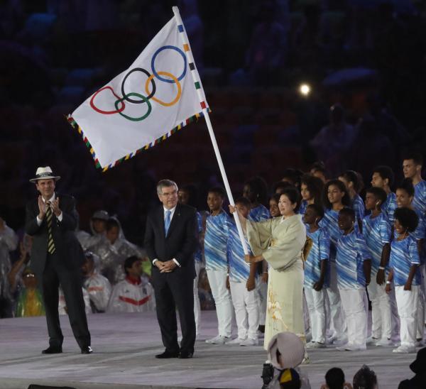 閉会式で五輪旗を受け取った小池百合子・東京都知事(前列右)。左端はパエス・リオデジャネイロ市長、中央はIOCのバッハ会長=21日、マラカナン競技場、林敏行撮影