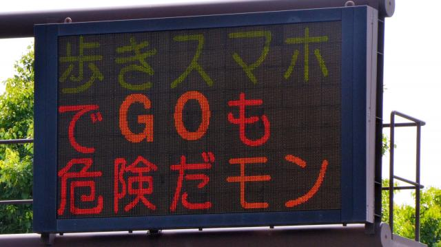熊本県警の電光掲示板に表示された「歩きスマホでGOも危険だモン」の文字=2016年7月26日