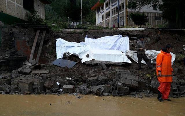 白い布で隠されているのが、崖崩れで露出してしまった墓の内部。遺体は土砂とともに道路へ流出したようです=イラン学生通信提供